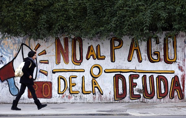 "A woman walks past a graffiti that reads ""No to the debt payment"" in Buenos Aires, July 28, 2014. Time is running out for Argentina to pay ""holdout"" investors suing Latin America's No. 3 economy for full payment on their bonds, or reach a deal that buys more time to avert a default. To match Insight ARGENTINA-DEBT/   REUTERS/Marcos Brindicci (ARGENTINA - Tags: POLITICS BUSINESS EMPLOYMENT)"